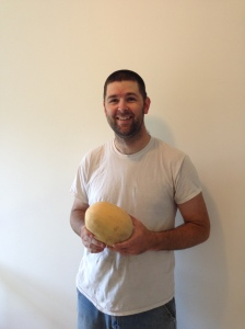 Chris with a cantaloupe from his garden.